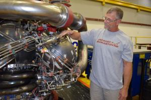 Owen Brayson (instrumentation tech for NASA's RS-25 prime contractor AR) exhibits the pogo accumulator assembly, NASA's largest 3-D-printed rocket engine component tested in the RS-25 production restart, on Engine 0528. (engine successfully tested 12/15)